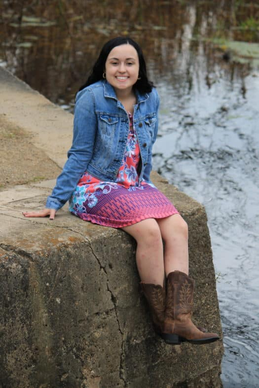 GVSU student Abbey wears a coral, pink, and purple summer dress with a medium-wash jean jacket and cowboy boots.