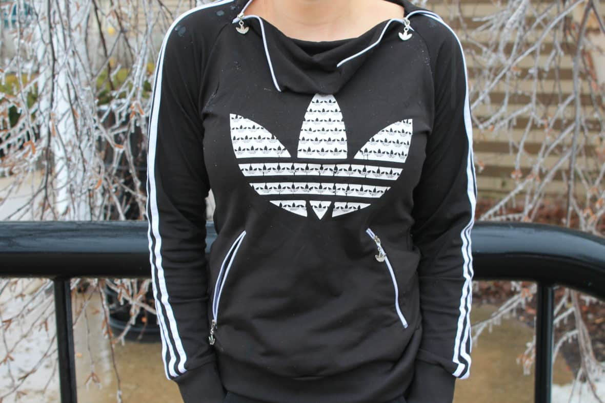 This GVSU student wears a black Adidas tracksuit hoodie with a cowl zipper collar and white detailing.
