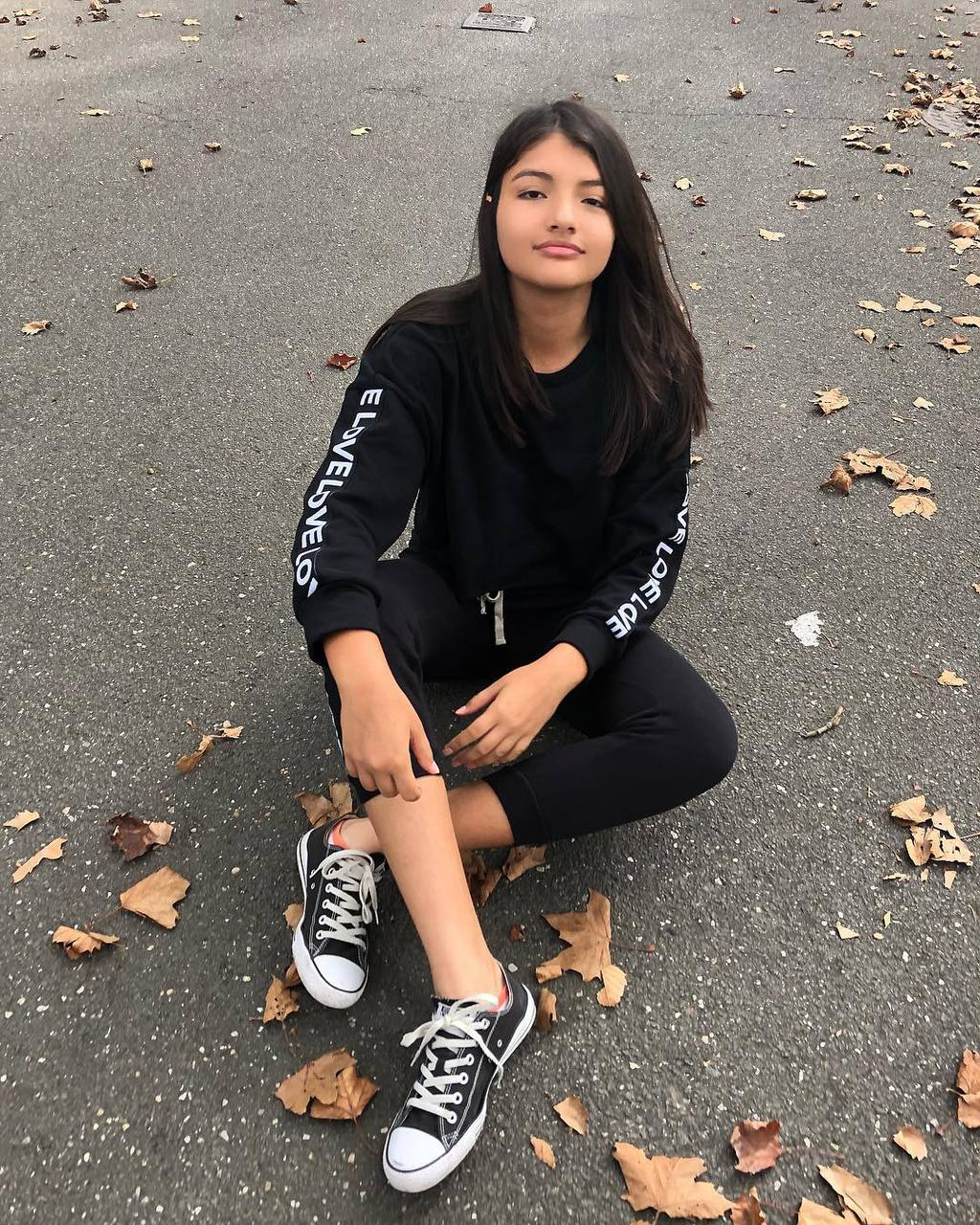 Nathaly wears a black matching sweatsuit with white words on the sleeves and matching black low-top Converse sneakers.