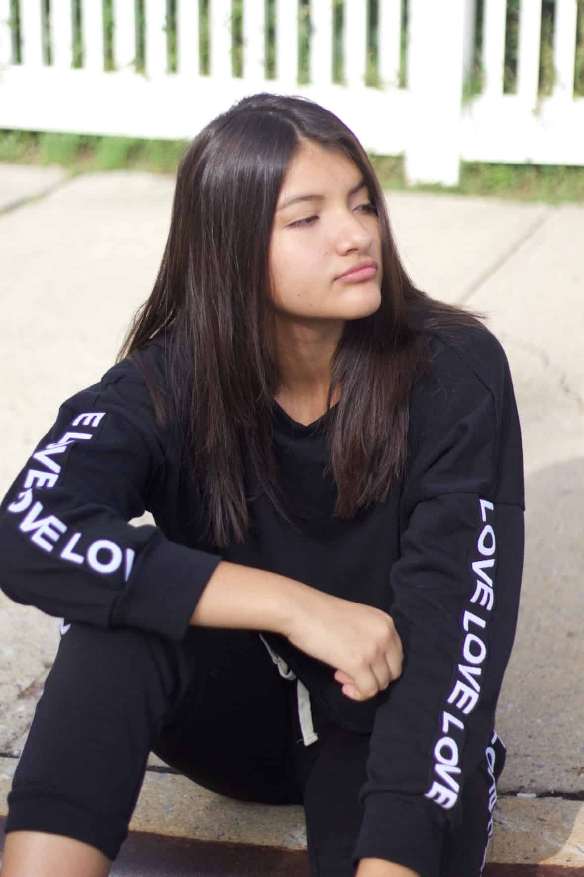 Nathaly wears a black and white tracksuit.