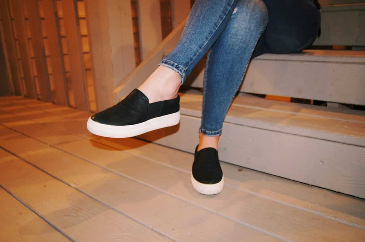 Renee wears black-slip-ons with large white soles and skinny faded jeans.