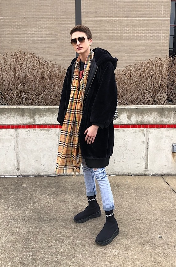 Fashion at WVU - student Kevin wears black sneakers, distressed jeans, a Burberry scarf, sunglasses, and an oversized black coat