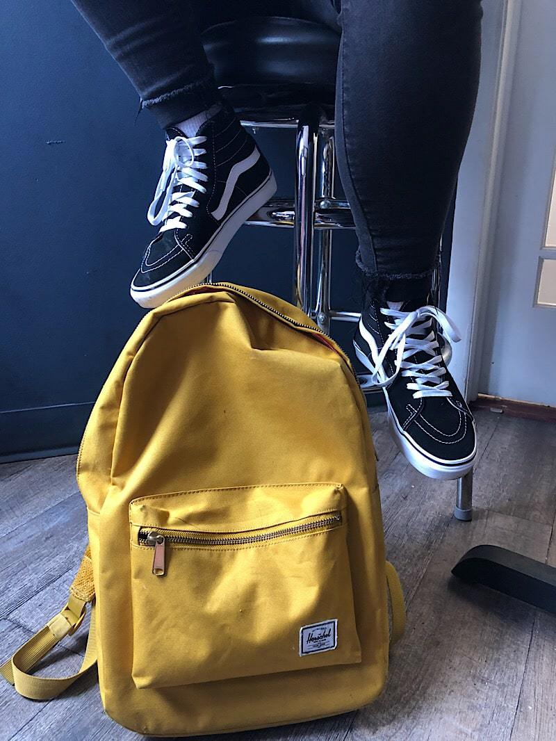 Tiana sports Vans Sk8-Hi sneakers and a yellow Hershel Supply Co. backpack.