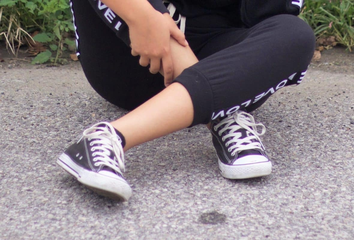 Nathaly wears black low-top Converse sneakers with white laces.