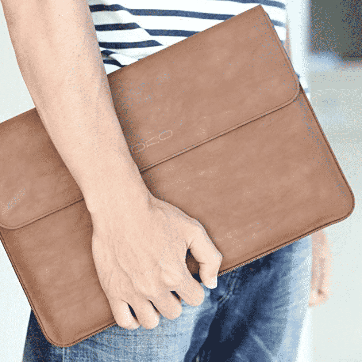 hand holding a leather laptop sleeve