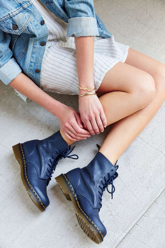 Chest-down shot of woman in dress, denim jacket, blue Dr. Martens boots, and gold bracelets and rings.