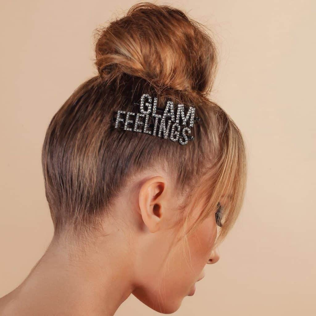Spring 2019 accessory trends: Close-up side view of woman with a topknot wearing embellished GLAM and FEELINGS hair clips