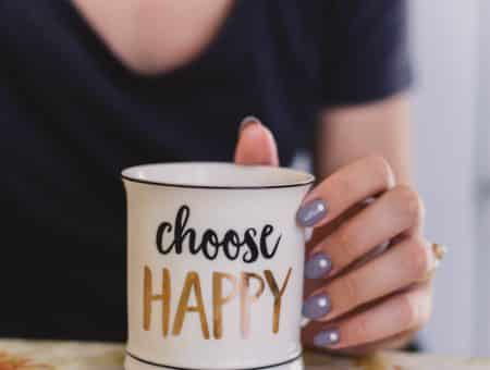 Girl holding a choose happy mug
