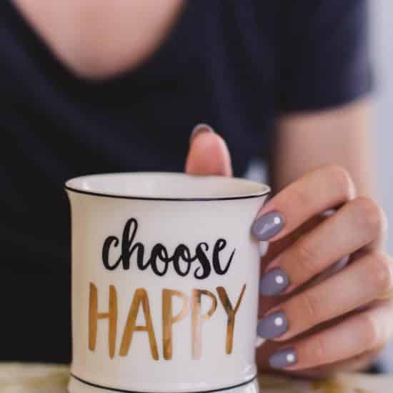 Girl holding a choose happy mug