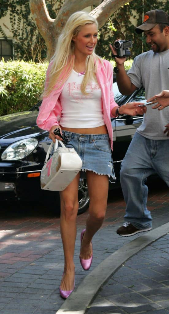 Paris Hilton 2000s style: Paris wears a t-shirt that says Paris Will you Go Out with me, a pink hoodie, a denim mini skirt, and pink high heels