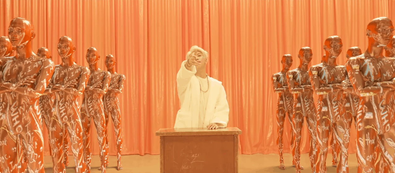 BTS persona video still - RM surrounded by robots in all white