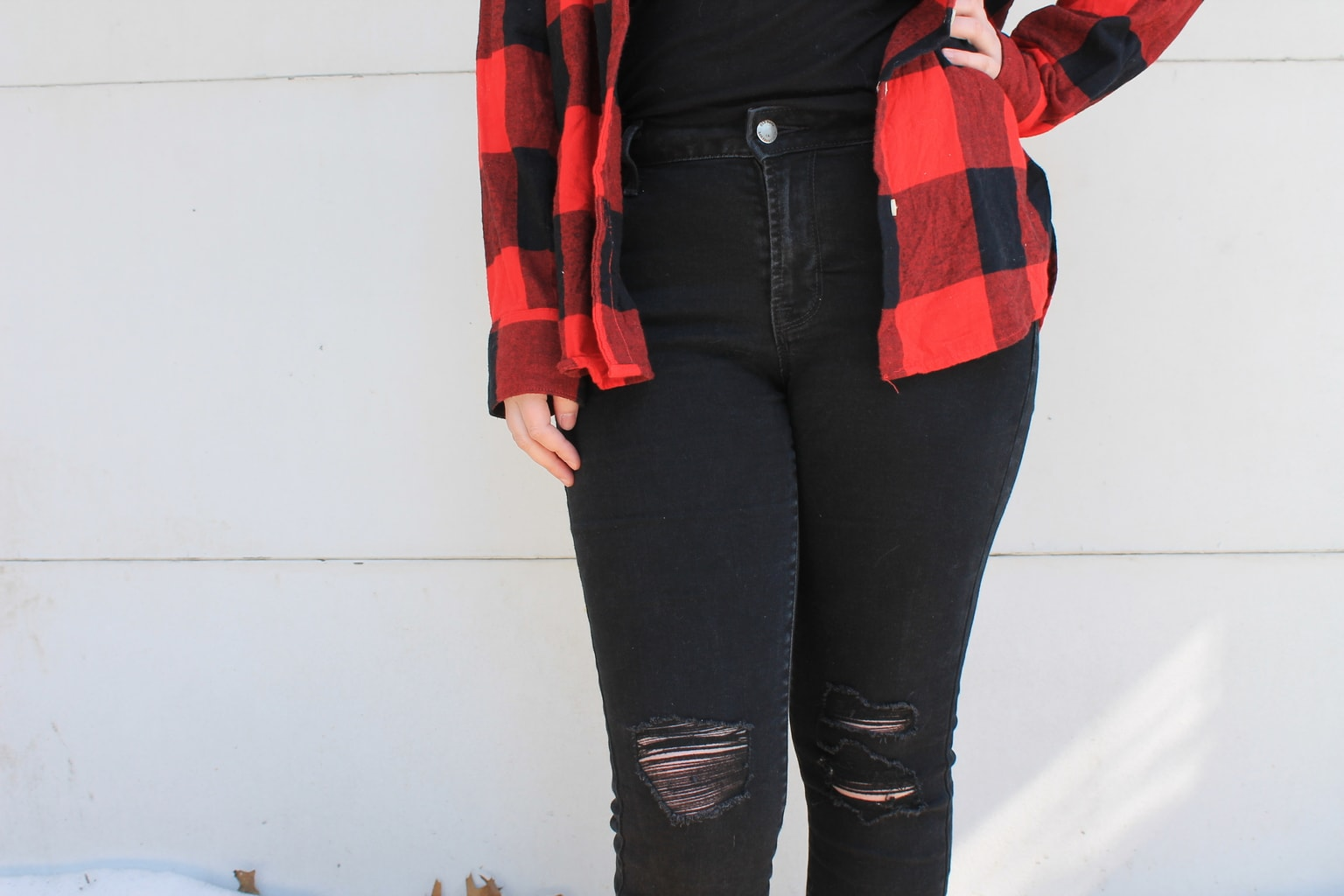 These high-waisted black denim jeans are distressed slightly around the knees.