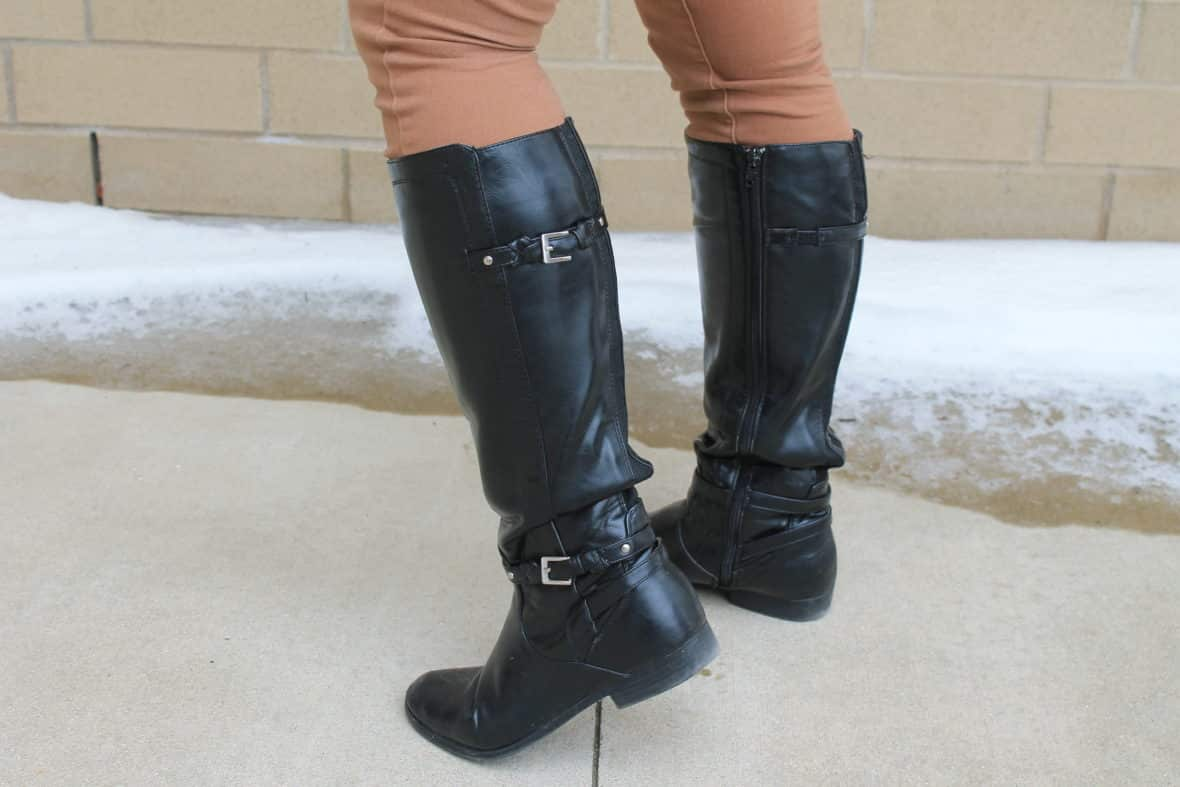 Leslie wears black riding boots with two buckles over her jeans.