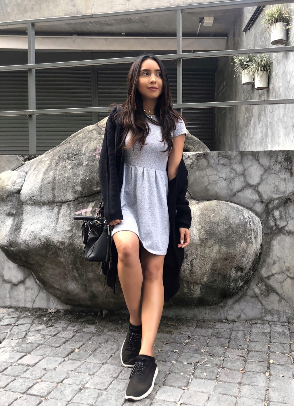 Cynthia wears a simple, grey, knit mini dress with a long, black Free People cardigan, and casual sneakers.