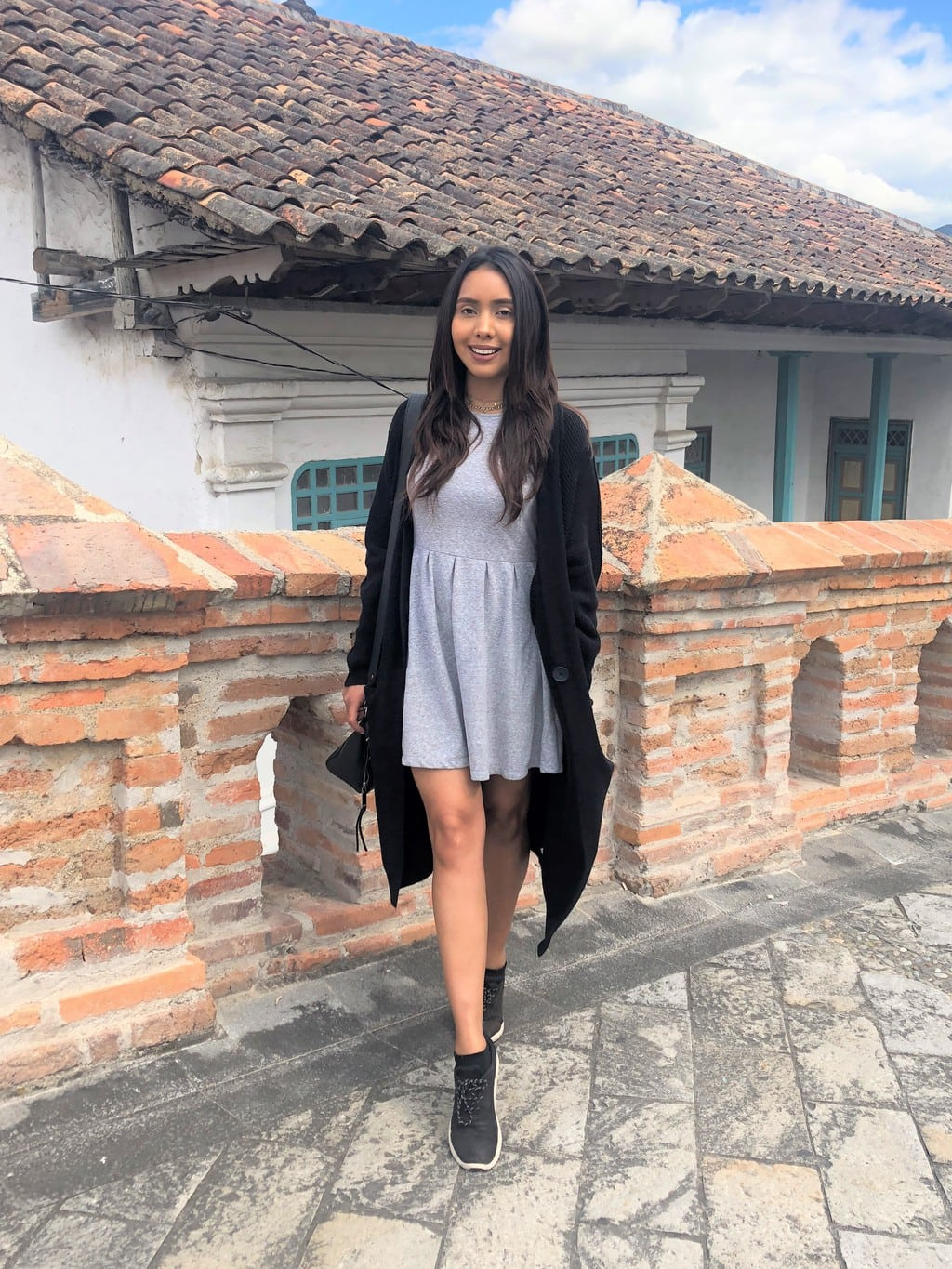 Cynthia wears a grey knit dress with a long, black cardigan, with black sneakers.