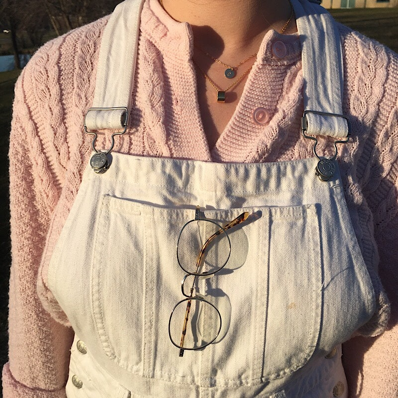 Abby wears thin brushed silver wire-rimmed glasses with her overalls.