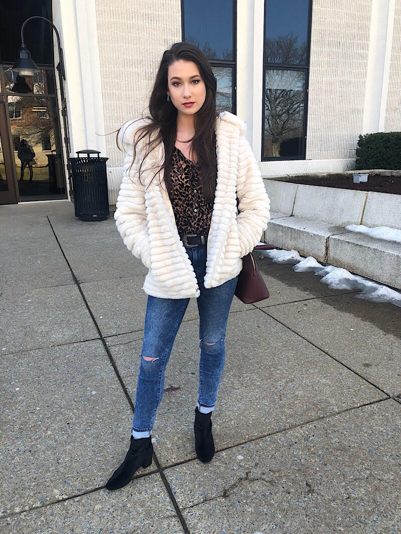 Bella wears a leopard print button-up shirt tucked into medium-wash cuffed skinny jeans, black boots, and a white furry coat.