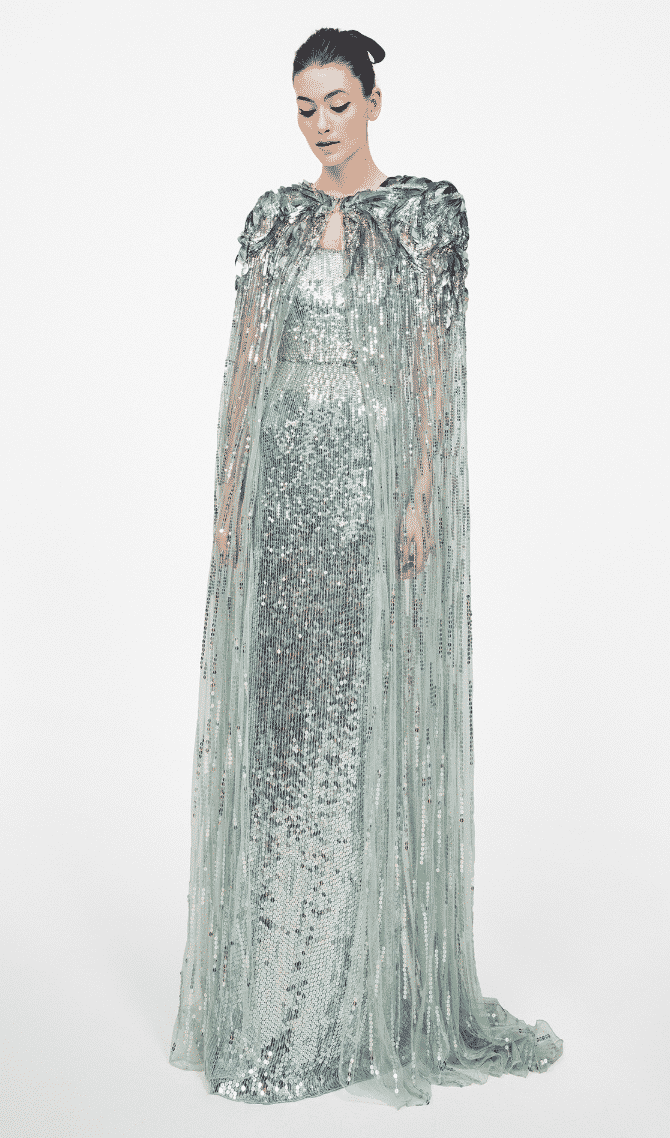 model wearing floor length gown covered in aqua and blue sequins with cape