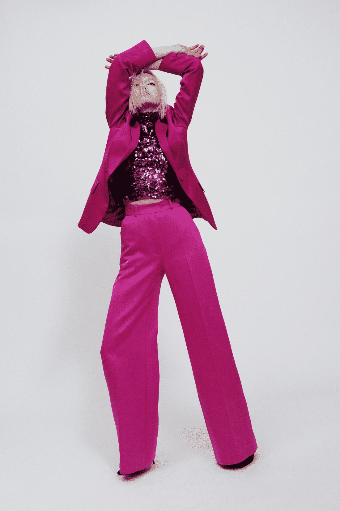 Model wearing magenta satin suit with sequin top