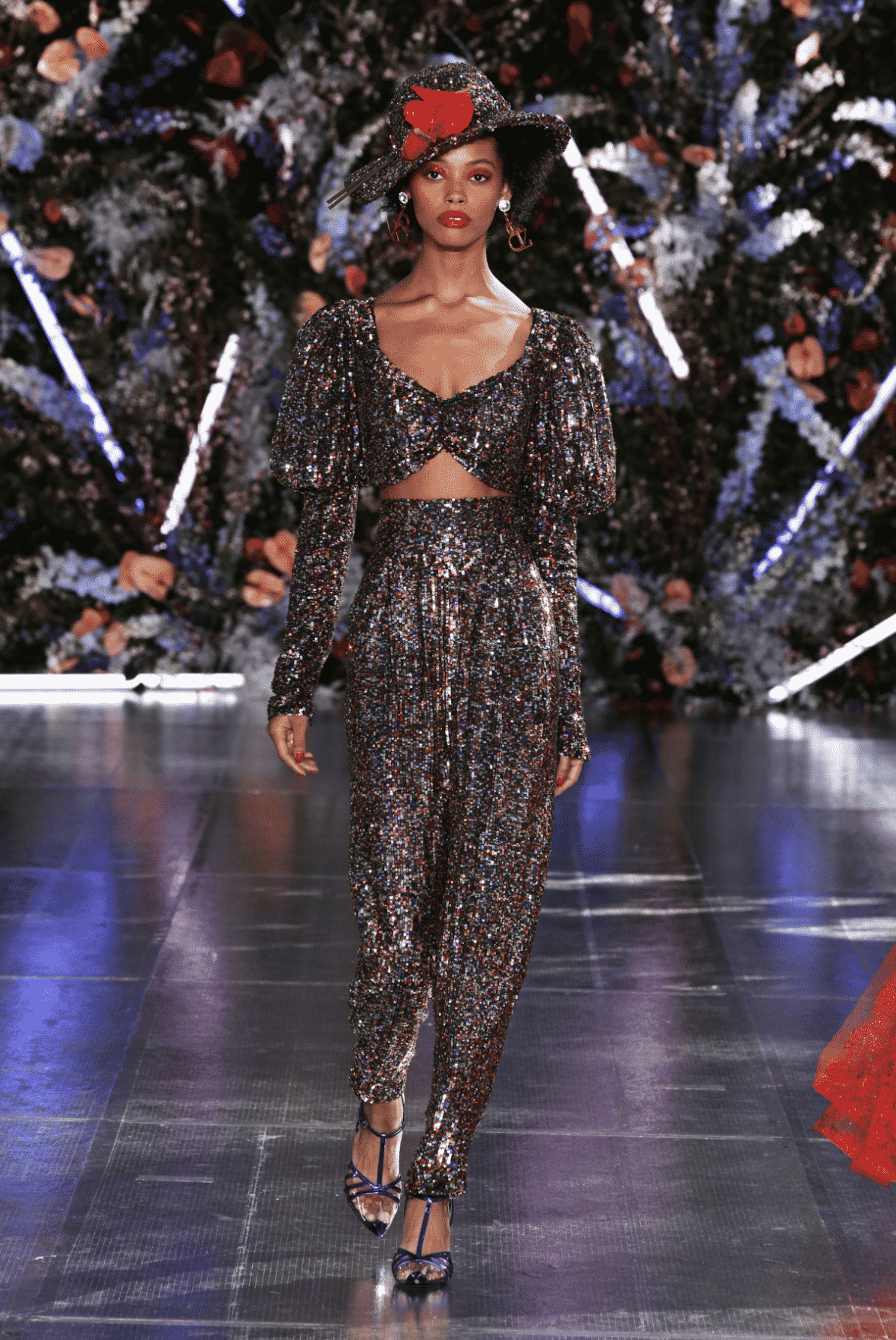 model wearing two piece crop top with balloon long sleeves and harem pants covered in multi colored sequins and sequin hat