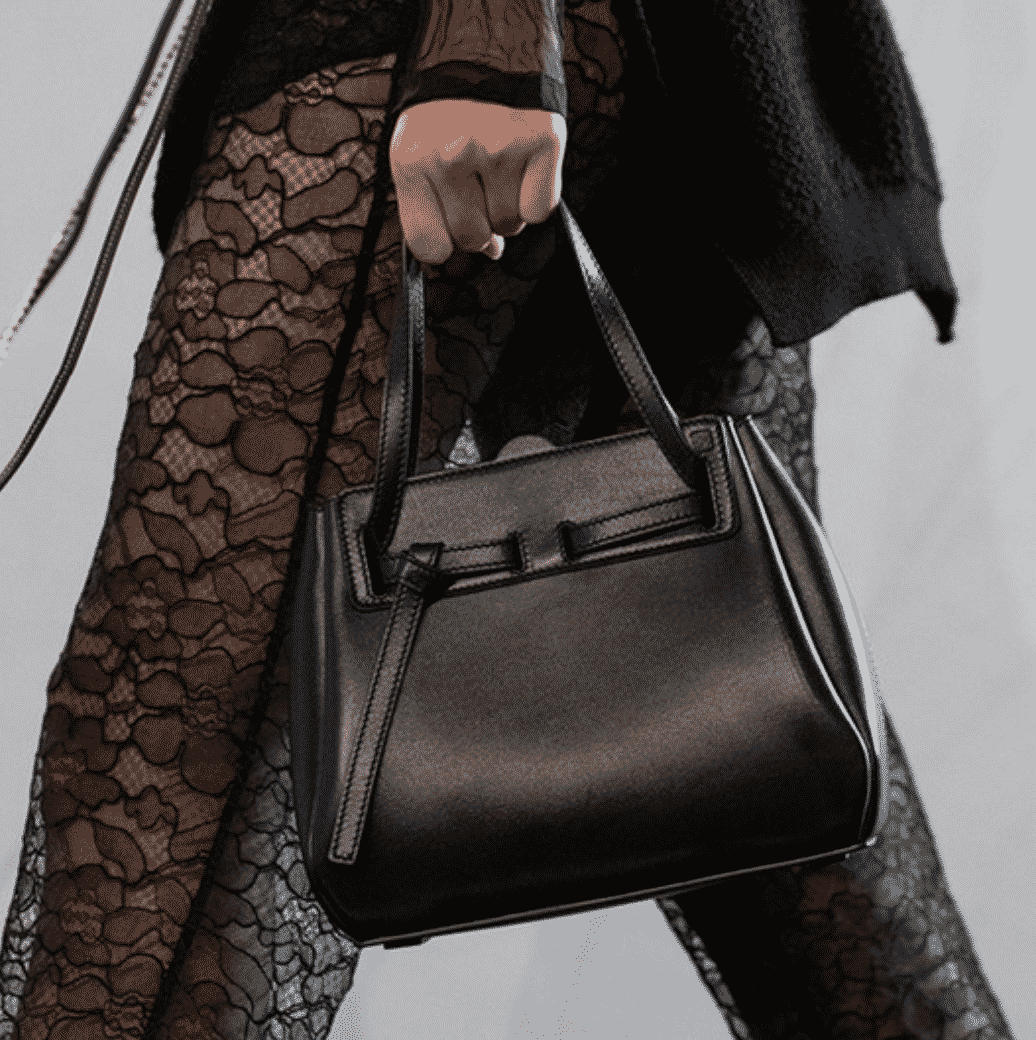 model carrying a black handbag