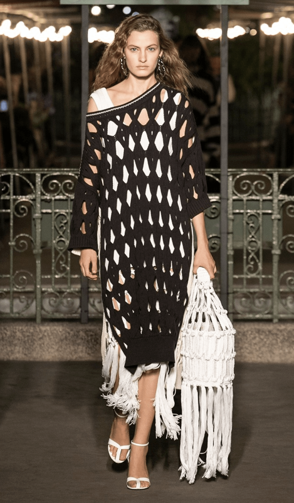 Model wearing a weaved poncho and carrying a weaved basket bag