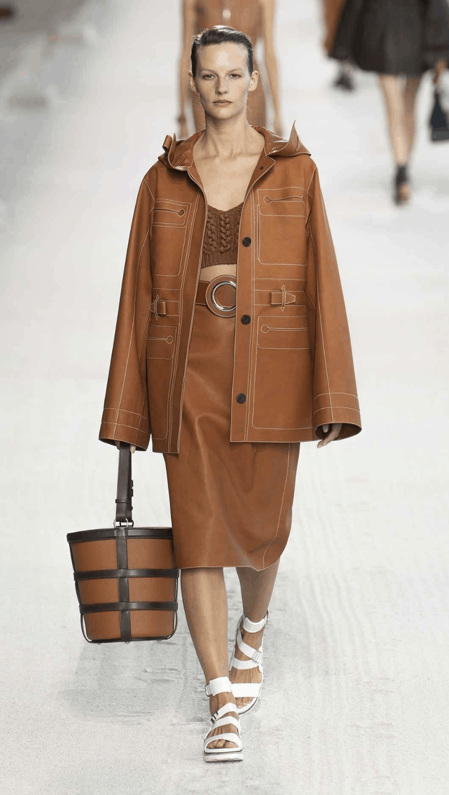 model wearing a skirt-suit and carrying a leather basket bag.