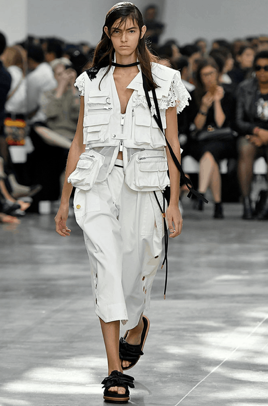 model in pocketed vest and white trousers