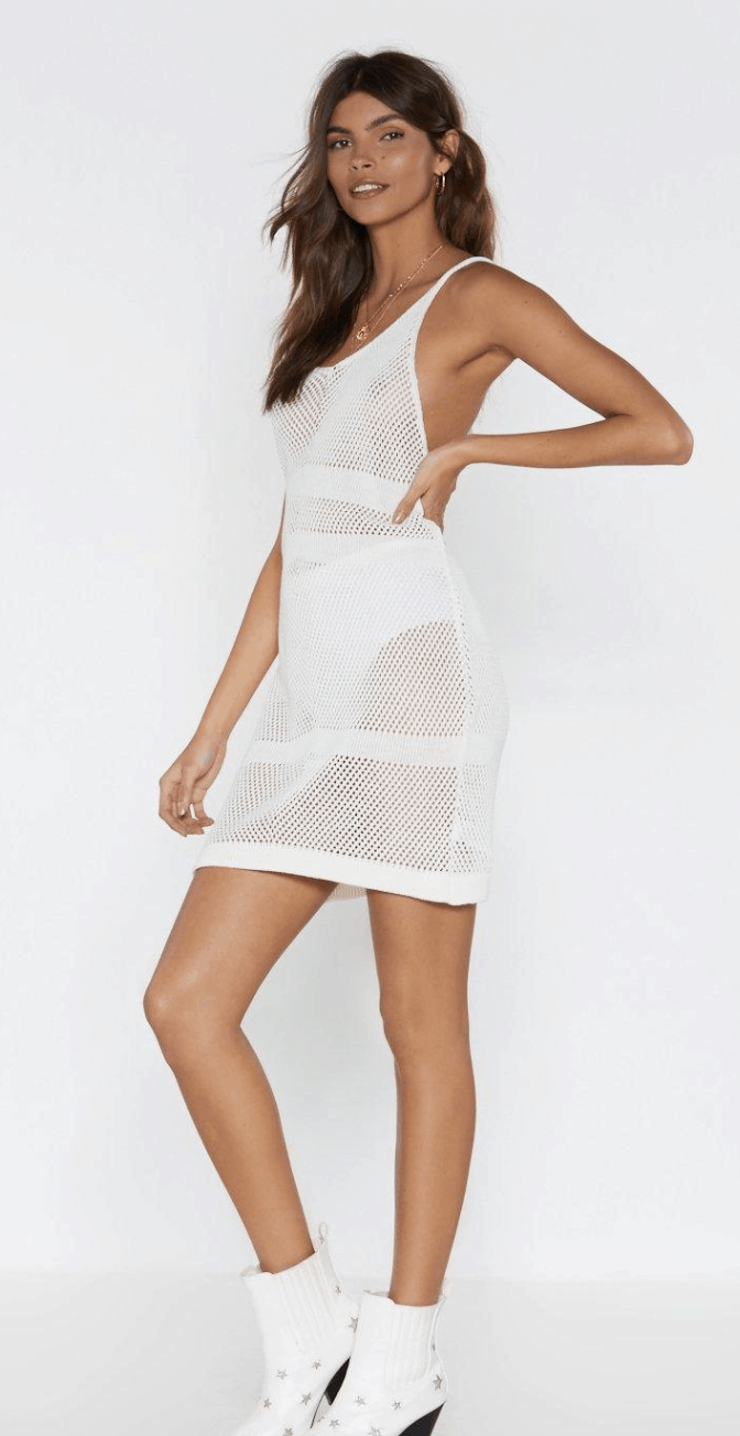 model in white net mini dress and white boots