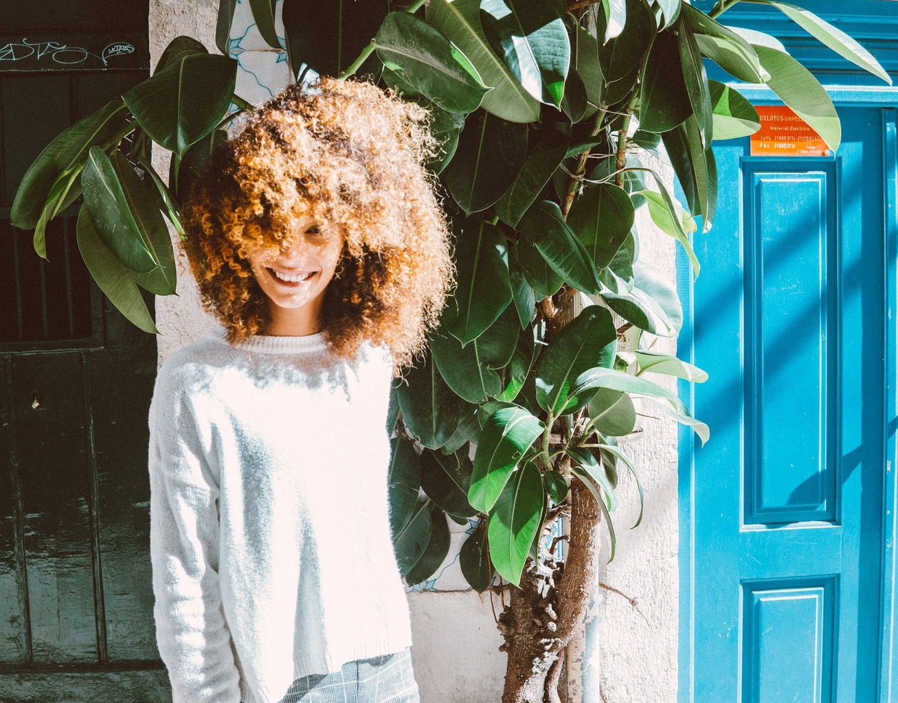 curly hair girl next to trees