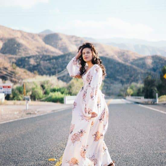 Woman in a long, floral-print dress standing on a road against a backdrop of mountains.