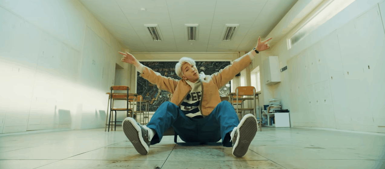 BTS Persona video screenshot - RM wearing jeans, sneakers, and a beige hoodie while sitting in a classroom