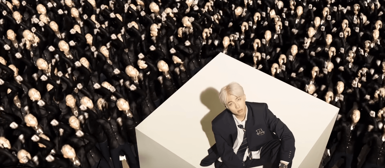 BTS persona video screenshot - RM in a black suit surrounded by clones