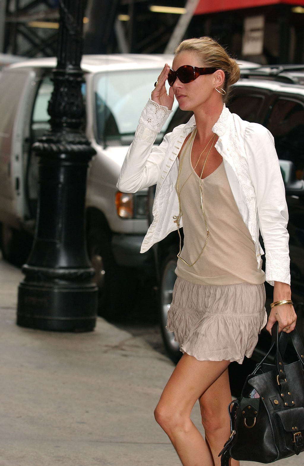 kate moss in a nude colored outfit and white jacket carrying a black tote bag