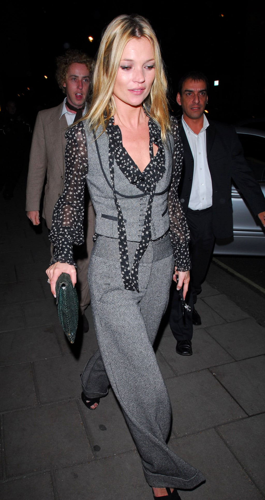 kate moss in a tailored menswear set and heels holding a clutch