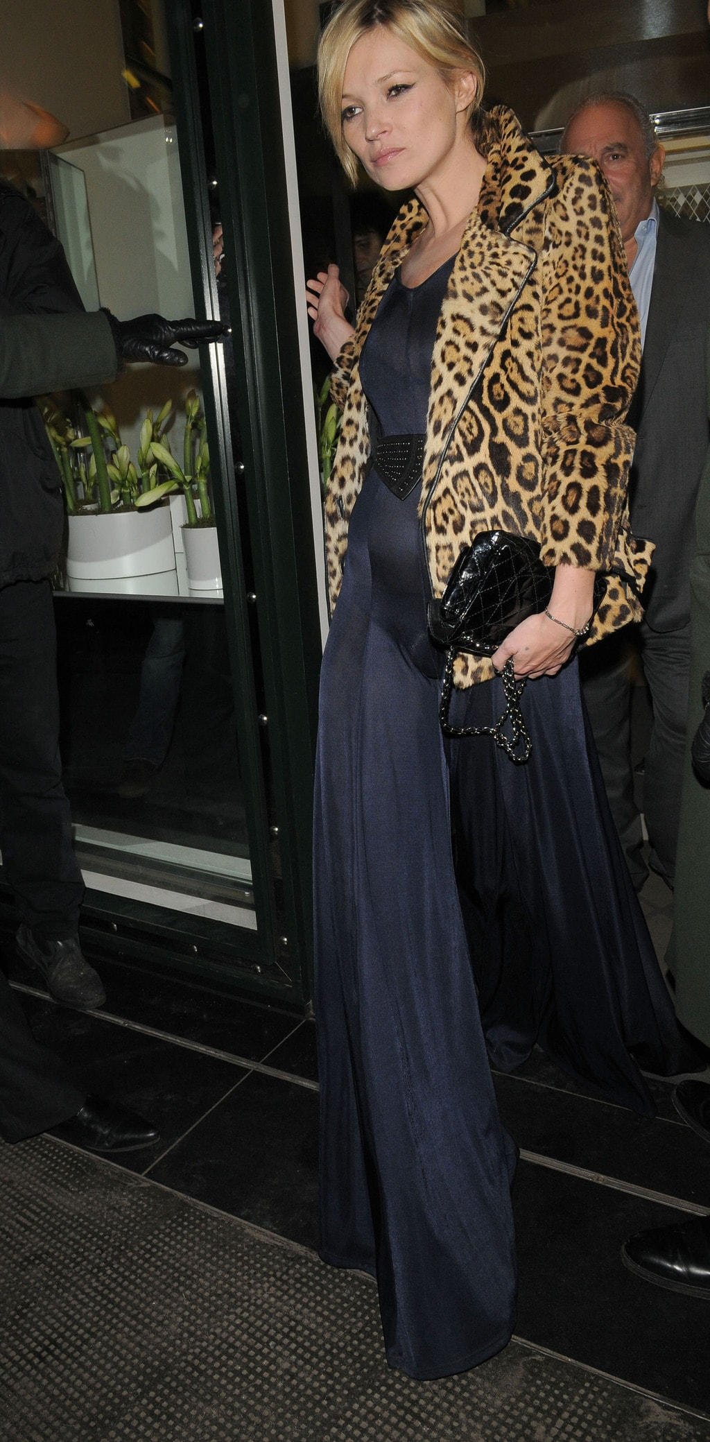 kate moss in a navy jumpsuit and leopard blazer carrying a clutch