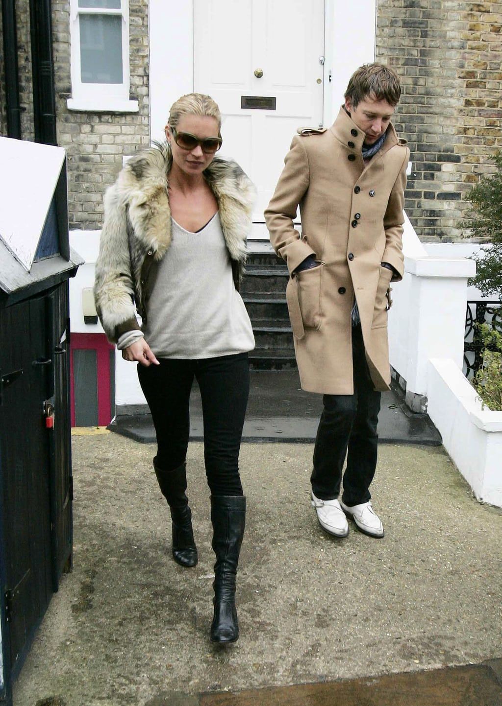 kate moss wearing boots, skinny jeans, a sweater, and fur jacket