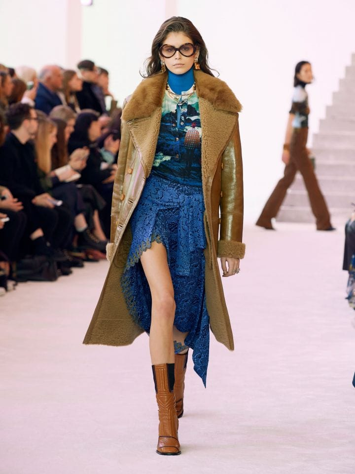 model in camel trench coat and blue layered tops and asymmetrical skirt