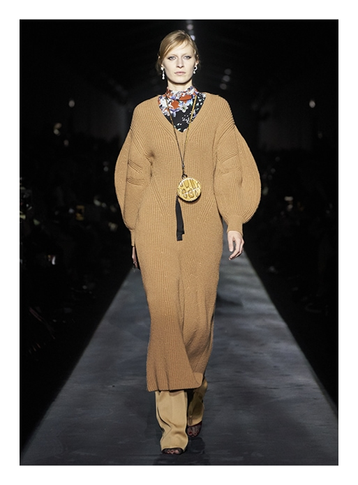 model in a camel sweater dress over a turtleneck and khaki pants