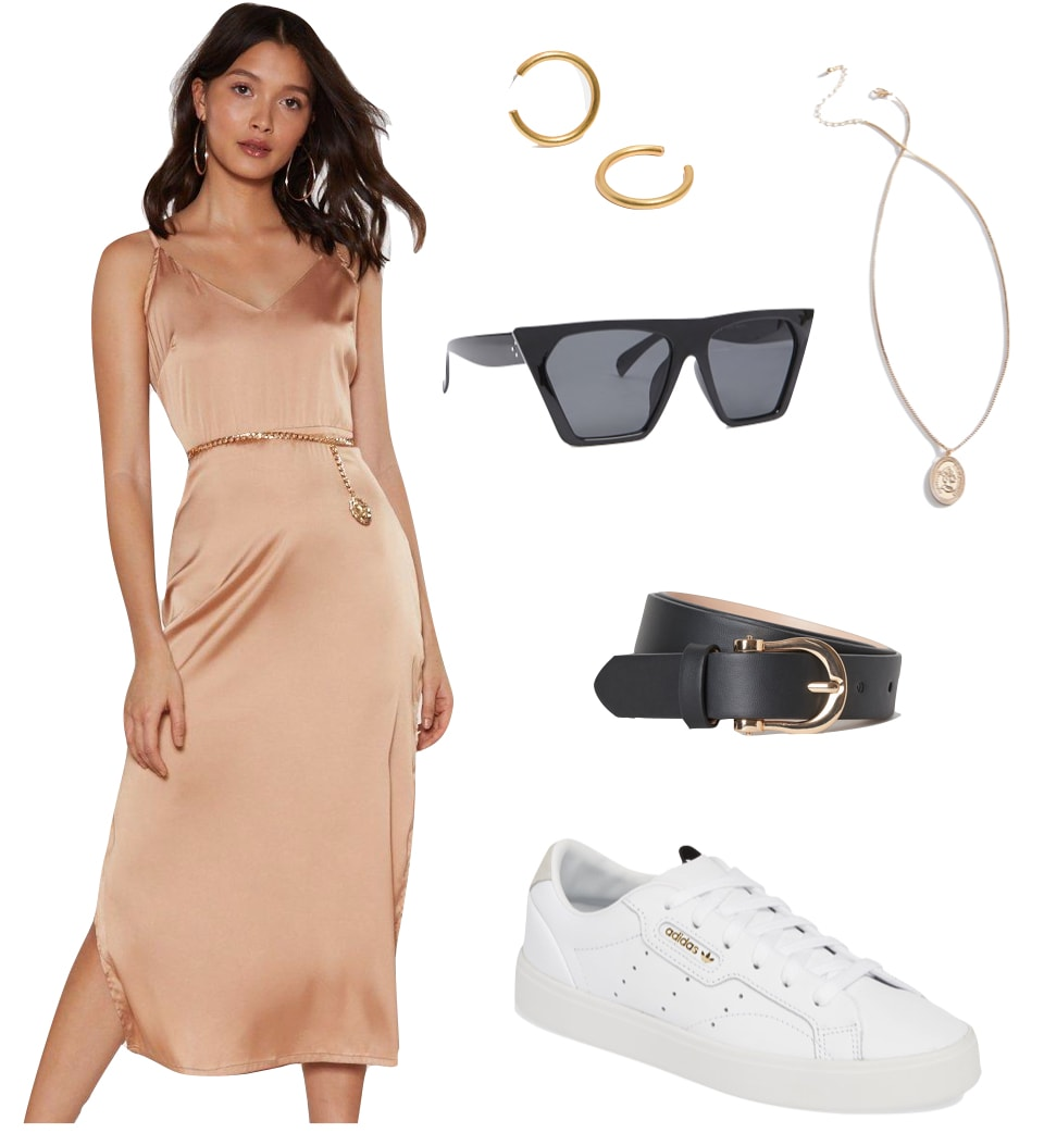 Hailey Bieber Outfit: beige satin midi slip dress, chunky gold hoop earrings, gold pendant necklace, black angular sunglasses, black and gold belt, and white low-top sneakers