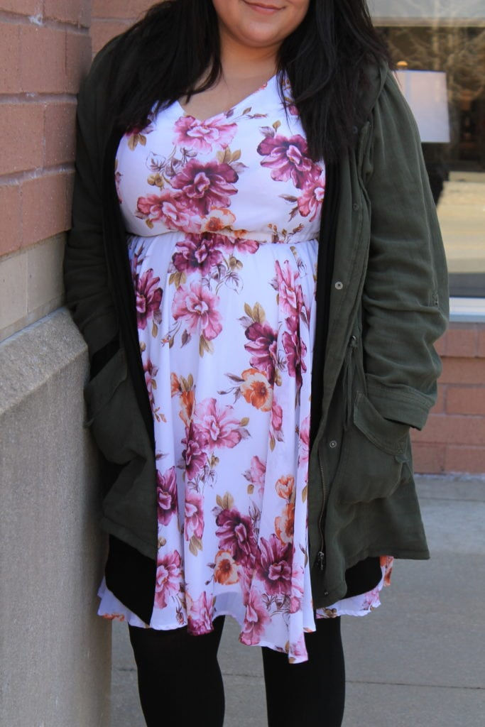 Katie wears a white and pink floral print sundress with a green jacket and black tights.