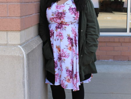 Katie wears a floral print sundress with an olive green jacket, black tights, and grey chunky-heeled lace-up booties.
