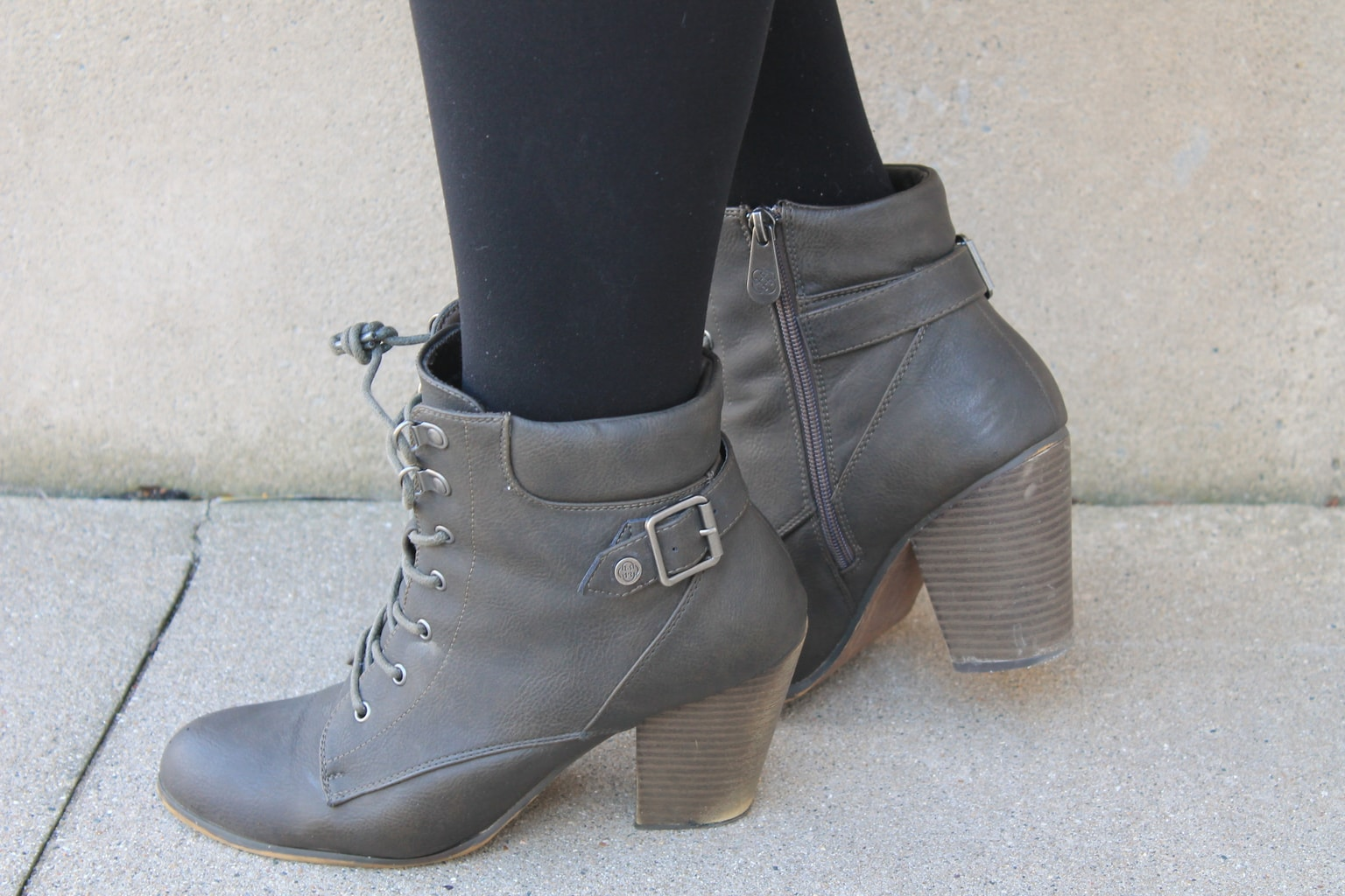 Katie sports grey chunky-heeled lace up booties with straps and buckles.