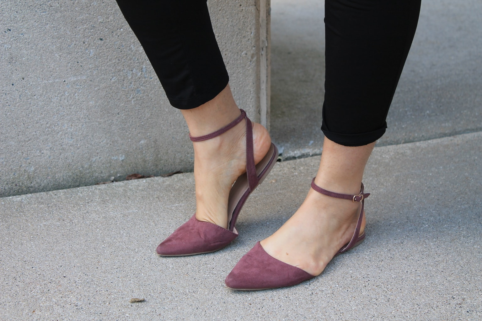 These pointed-toe flats are mauve and have an ankle strap.