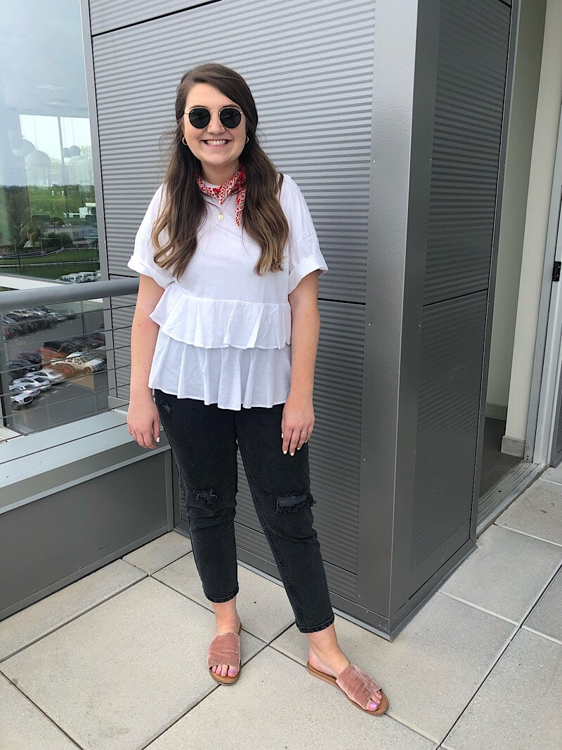 Ali, a student at West Virginia University, wears a layered ruffle white shirt with short sleeves, a red bandana ascot, round sunglasses, black cropped jeans, and flat blush velvet slide sandals.