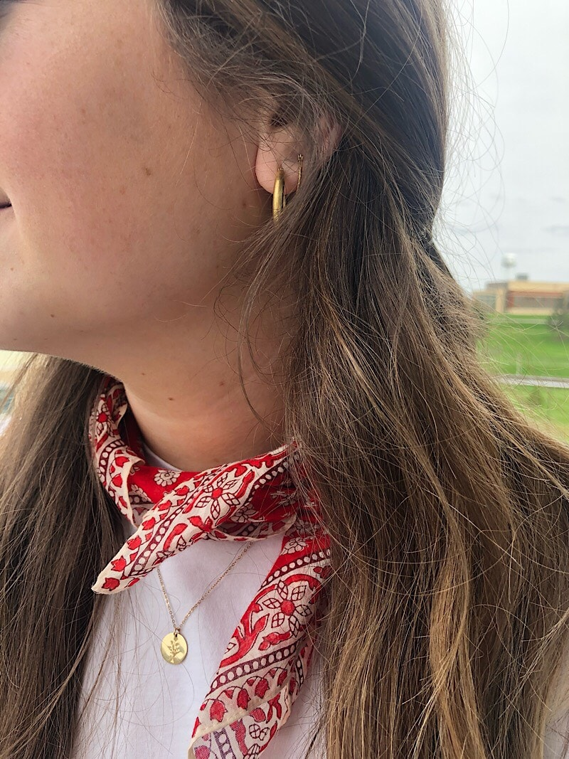 Ali wears gold Madewell hoops, a dainty GLDN pendant necklace, and a bright red bandana around her neck.