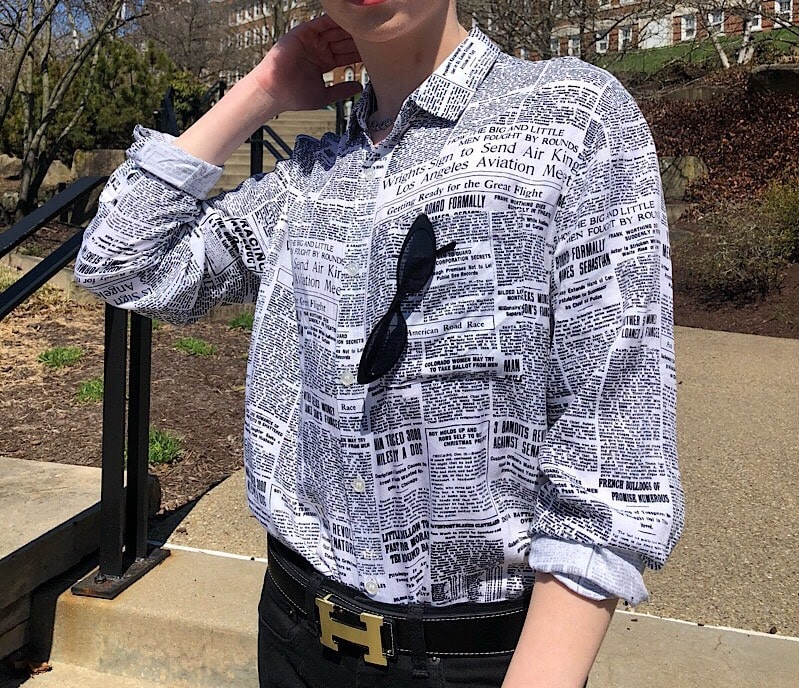 Caleb wears a button-up shirt in black and white newspaper print with an Hermes belt buckle.