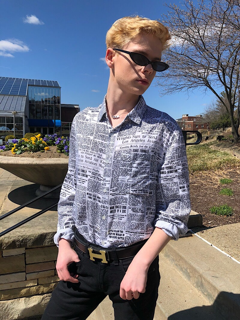 Caleb wears skinny black plastic framed sunglasses with his newspaper print button-up shirt and Hermes belt.