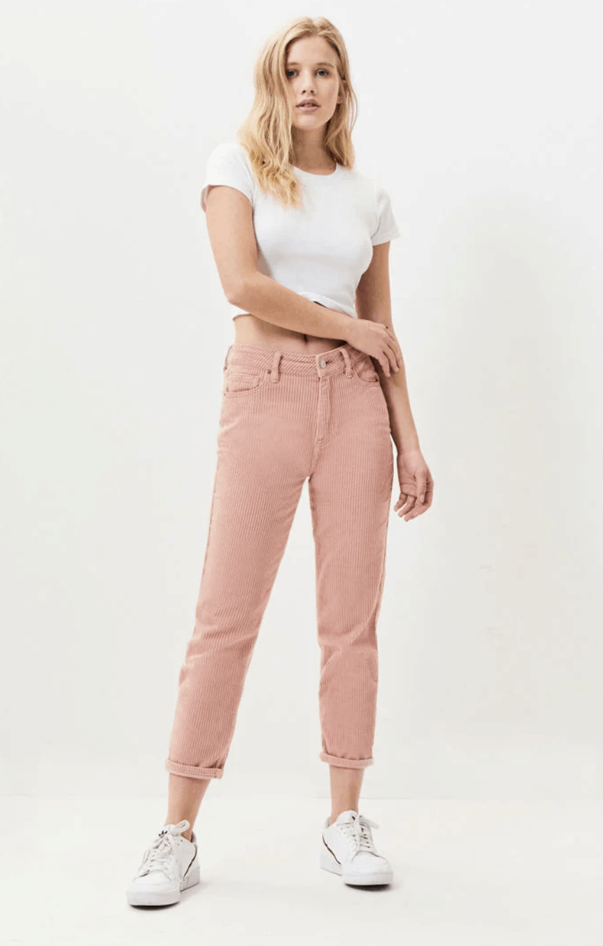 model in white cropped tee and pink corduroy pants