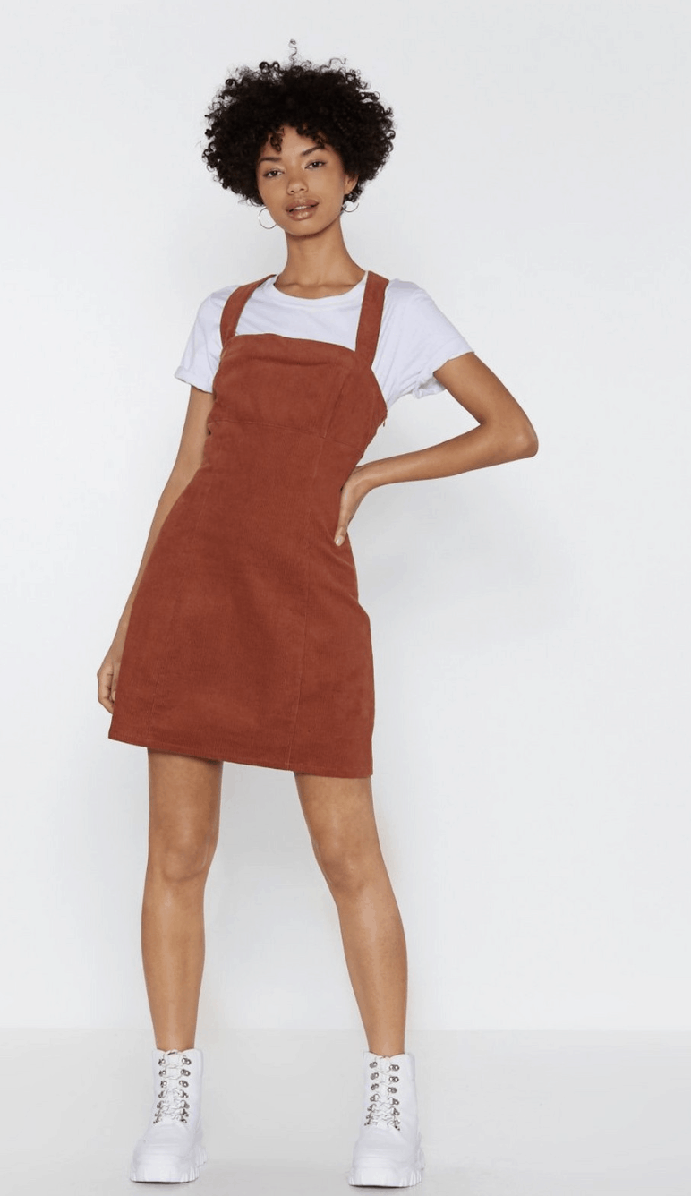 model wearing a corduroy dress and white tee with white sneakers